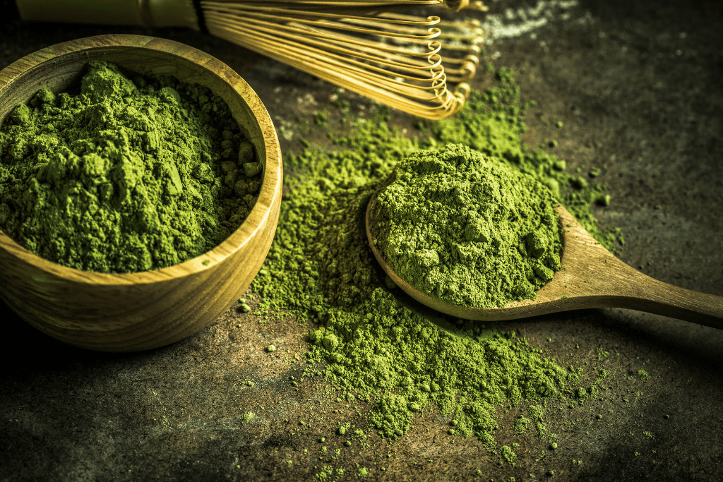 matcha tea powder on a spoon with bowl and whisk