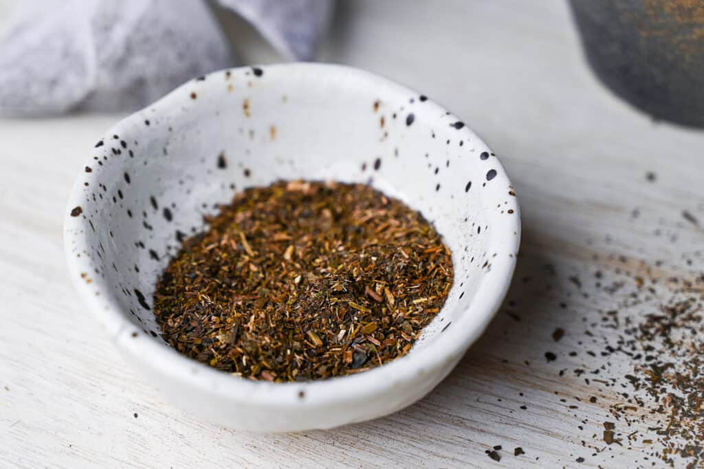 a close up of loose hojicha roasted green tea in a small speckled dish