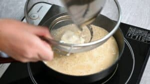 pouring ice cream custard mixture through sieve