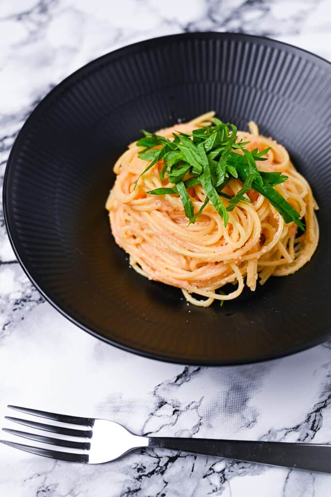 mentaiko pasta served in a black pasta dish with fork