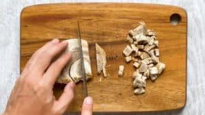 cutting chashu on wooden chopping board