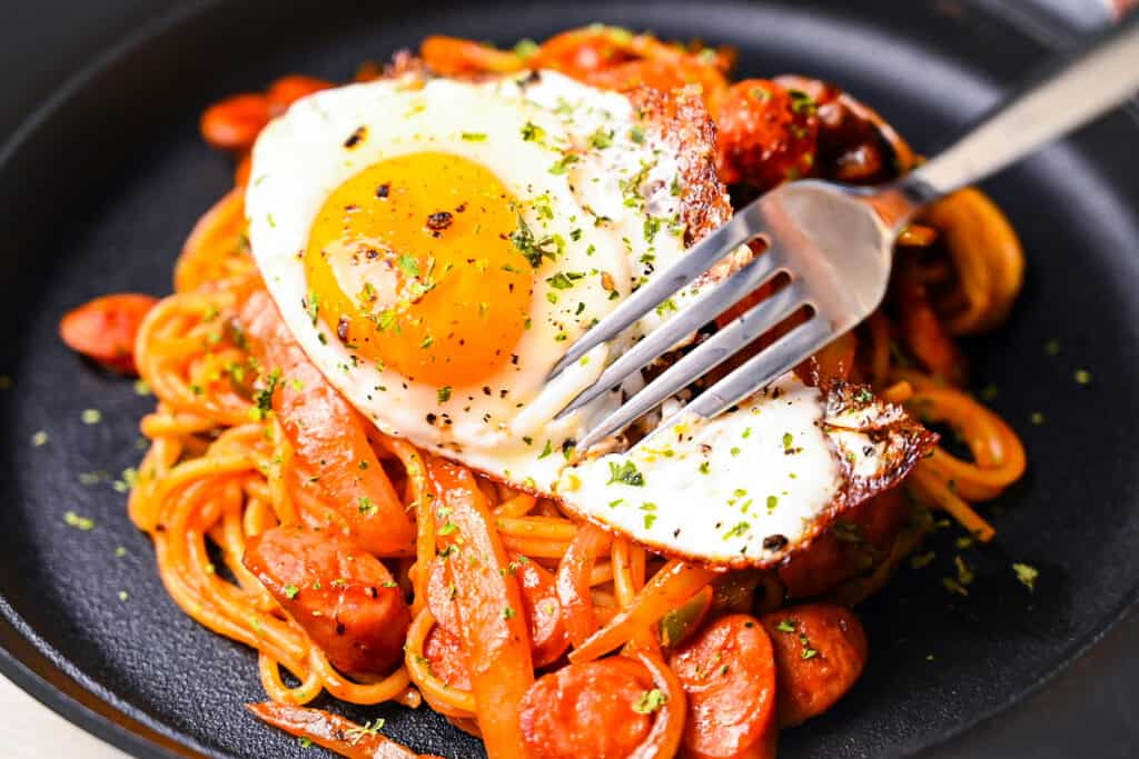 Fork cutting into fried egg on Spaghetti Napolitan (ketchup pasta)