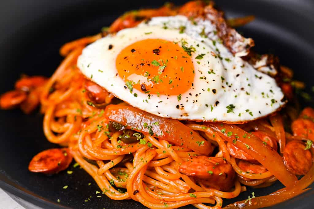 Spaghetti Napolitan (ketchup pasta) on a black plate topped with a fried egg close up