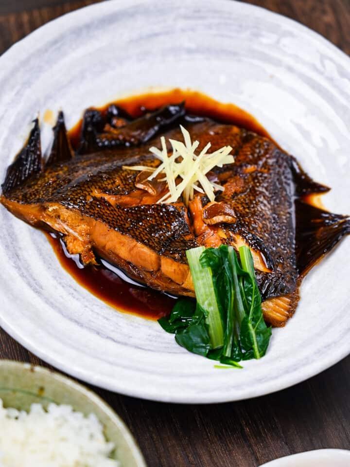 Sakana no nitsuke Japanese simmered fish on a white plate with ginger and bok choi