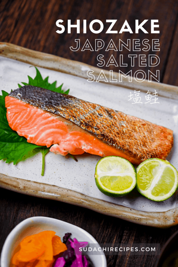 Shizake Japanese Salted Salmon served on a pale rectangular plate with sudachi and shiso leaves