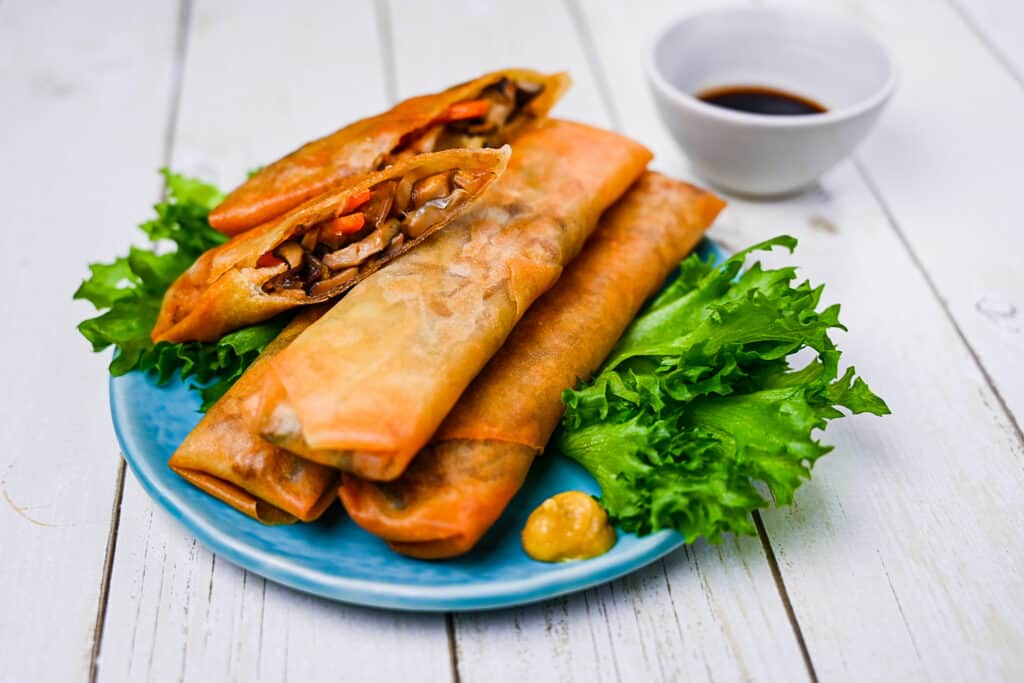Japanese Harumaki Spring Rolls on a blue plate with frilly lettuce