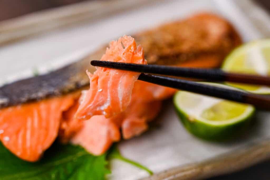 A piece of shiozake salted salmon held with black chopsticks
