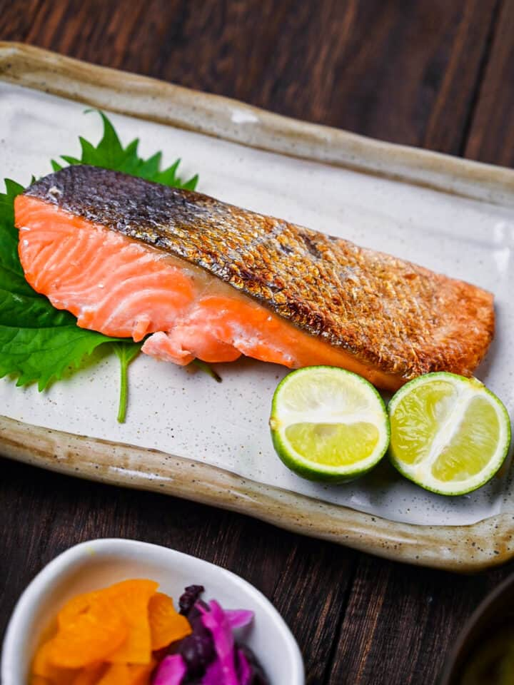 Shizake Japanese Salted Salmon served on a pale rectangular plate with sudachi and shiso leaves featured image