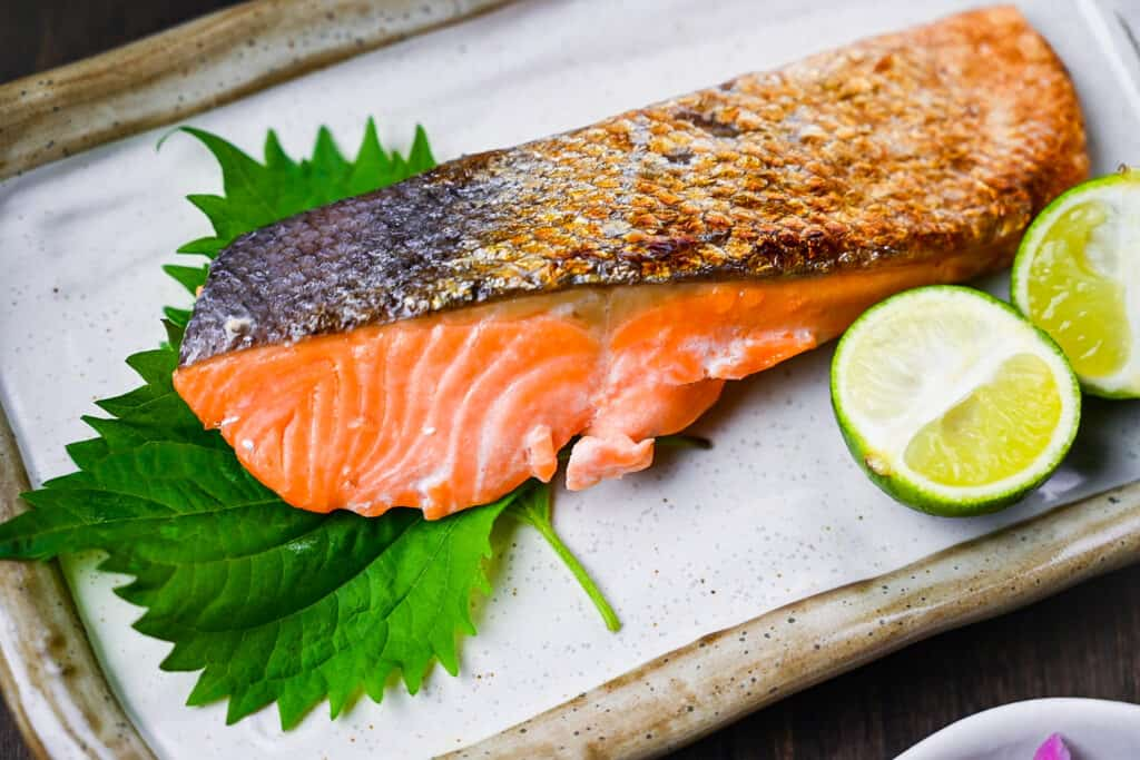Shizake Japanese Salted Salmon served on a pale rectangular plate with sudachi and shiso leaves right side