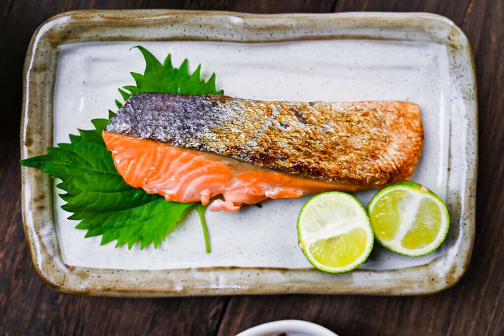 Shizake Japanese Salted Salmon served on a pale rectangular plate with sudachi and shiso leaves top down