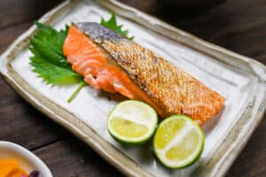 Shizake Japanese Salted Salmon served on a pale rectangular plate with sudachi and shiso leaves left side view