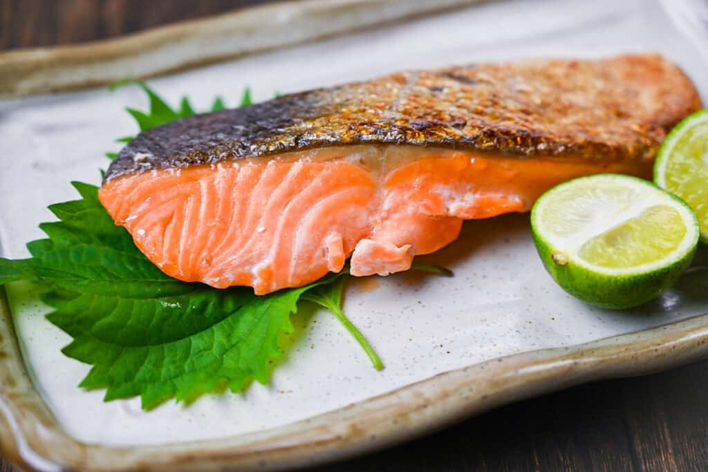Shizake Japanese Salted Salmon served on a pale rectangular plate with sudachi and shiso leaves closeup