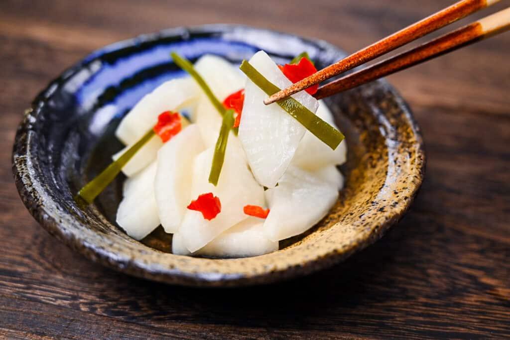 Bettarazuke pickled daikon held with wooden chopsticks