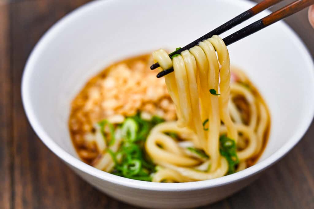 Udon noodles held with wooden chopsticks