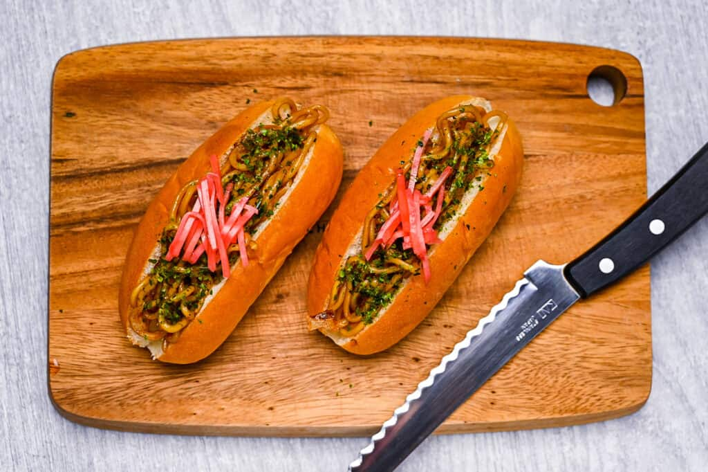two yakisoba pans on wooden chopping board top down view